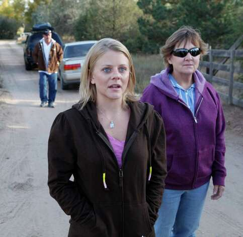 Tiffany Hartley, center, arrives at her parents home in LaSalle, Colo., on Saturday, Oct. 23, 2010, with her mom Cynthia, right, and father Bob Young, left, after riding with them from Texas.  Hartley's husband was shot and believed killed while the couple were jet skiing on Falcon Lake last month.  David Hartley's body has not been recovered. Photo: AP