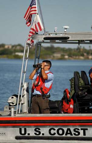 A man on a U.S. Coast Guard uses binoculars on Falcon Lake, a lake that straddles the U.S. Mexico border, where where Coloradan David Hartley is still missing, Thursday, Oct. 7, 2010 in Zapata, Texas. Hartley's wife says her husband was shot to death by Mexican pirates chasing them on speedboats across the lake on Sept. 30 as they returned on Jet Skis from a trip to photograph a historic Mexican church. Photo: AP