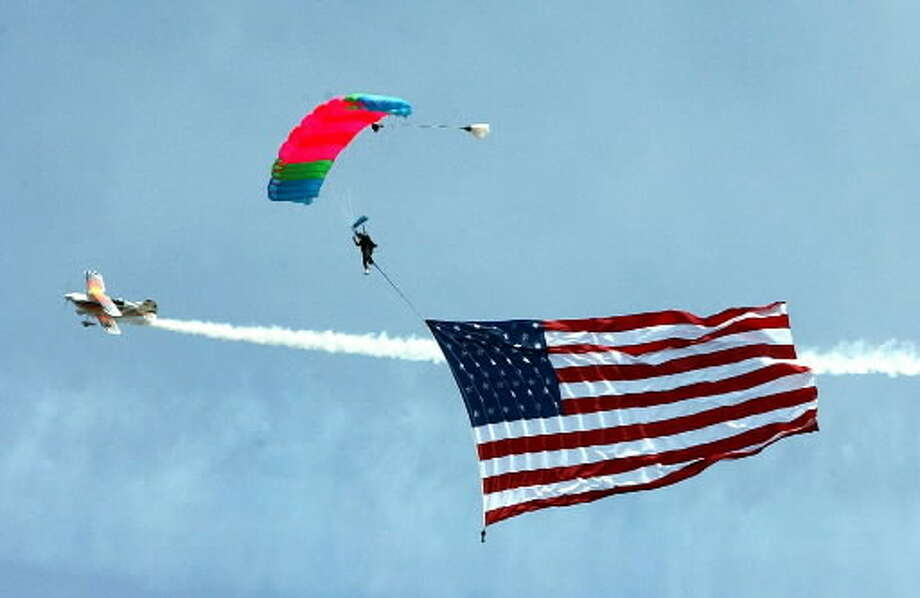 In this photograph from September 2001, Mohawk Valley parachutist Bob Raecke carries an American Flag with him while jumping from an airplane at the Schenectady Airshow. The Saratoga County Sheriff's Office said Raecke intentionally unhooked his parachute when he jumped from a plane on Sunday, Sept. 18, and plunged to his death. (File photo)