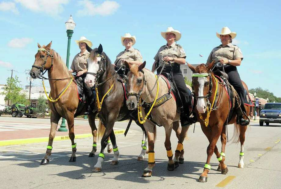 DAVID HOPPER: FOR THE CHRONICLE TROTTING ALONG: Members of the Montgomery County Precinct 2 Mounted Patrol, JoDean Janczak, Marilyn Kinney, Linda Young, and Vickie Voelz, practice precision riding and crowd control in downtown Conroe. Photo: David Hopper / freelance
