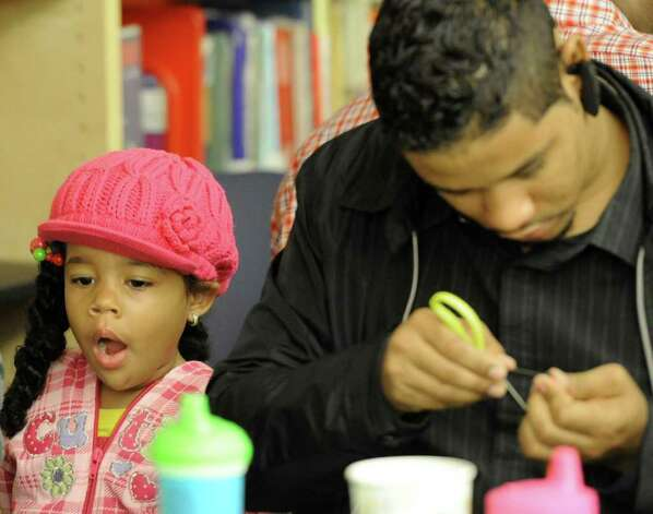 Nairobie Ramerez, 4, yawns as her father Antonio works on a project at the Delaware Community School in Albany, N.Y. September 20, 2011, during a program to get father figures more involved with their children.  The Albany School District is joining with schools statewide in the event, a partnership with the New York State Fatherhood Initiative of the State Office of Children and Faily Services and Office of Temporary and Disability Assistance. (Skip Dickstein/Times Union) Photo: Paul Grondahl / 00014694A