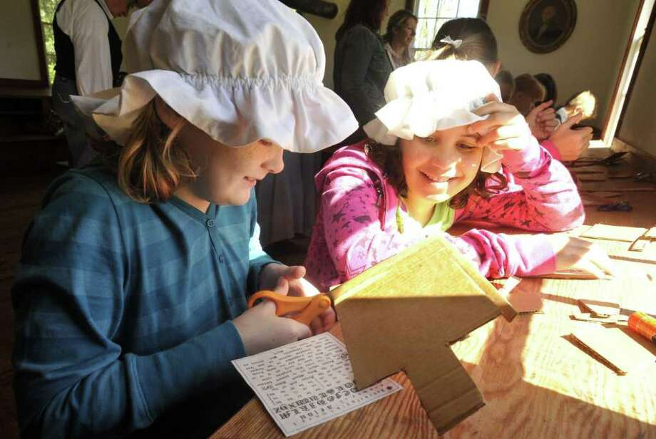 Hailey Wilson, 9, left, and Genny Kelly, 8, construct hornbooks, originally primers made with animal horn, during Children's Day at the Little Red Schoolhouse in Newtown Sunday, Sept. 18, 2011. Photo: Michael Duffy
