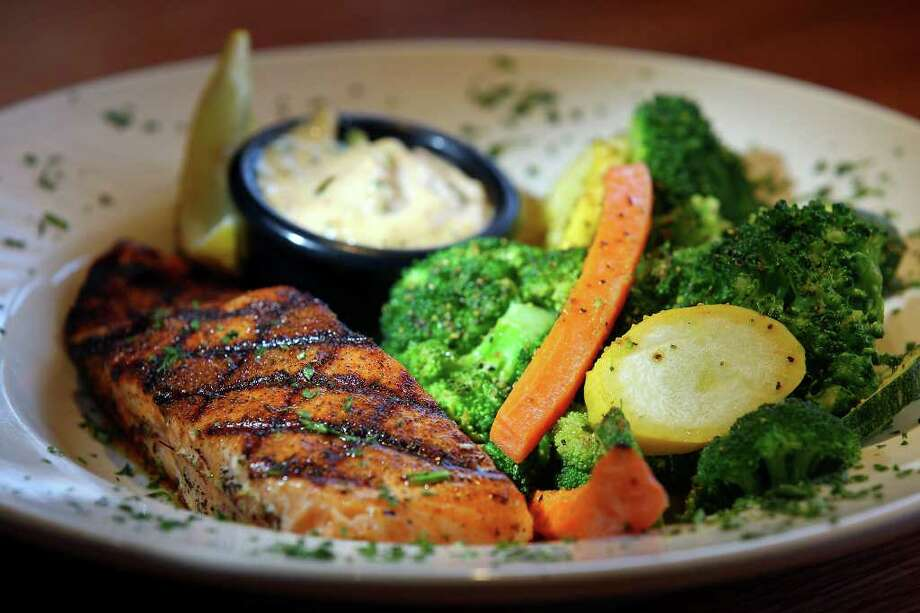 The Blackened Atlantic Salmon is available with a choice of salads and a choice of loaded baked potato or steamed fresh vegetables. Photo: EDWARD A. ORNELAS, SAN ANTONIO EXPRESS-NEWS / © SAN ANTONIO EXPRESS-NEWS (NFS)