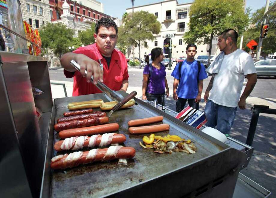 Matthew Tristan cooks dogs at the family-operated Alamo Hot Dog Co. cart at the corner of Commerce and Navarro. Photo: BOB OWEN, SAN ANTONIO EXPRESS-NEWS / rowen@express-news.net