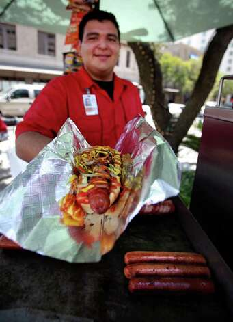Matthew Tristan serves up a custom hotdog from his family operated Alamo Hot Dog Co. cart at the corner of Commerce and Navarro. Photo: BOB OWEN, SAN ANTONIO EXPRESS-NEWS / rowen@express-news.net
