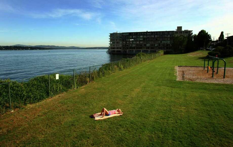 A sunbather relaxes at a small park at the intersection of 43rd Avenue East and East Lynn Street in Seattle's Madison Park neighborhood on Tuesday, September 20, 2011. A fence limiting access to Lake Washington may be removed. Photo: JOSHUA TRUJILLO / SEATTLEPI.COM