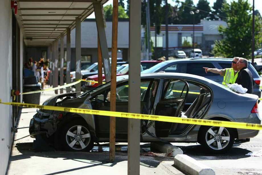 Investigators look over the scene where a car slammed into the side of the Jo-Ann Fabric and Craft store on Aurora Avenue North in Shoreline on Tuesday, September 20, 2011. Three elderly women were in the car at the time of the accident. One woman was killed and two were critically injured in the accident. Photo: JOSHUA TRUJILLO / SEATTLEPI.COM