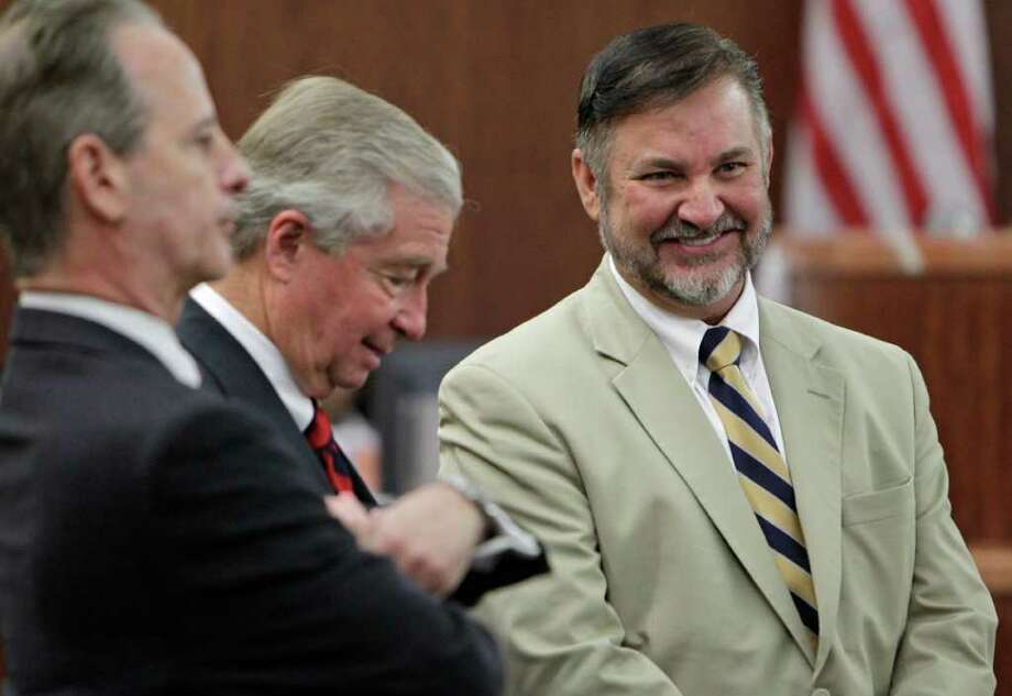 Criminal defense attorneys Brian Wice, left, Dick Deguerin, center, and client Michael Brown, right, react after Brown was found not guilty of assault in a trial at the Harris County Criminal Justice Center.  Brown, a former hand surgeon, was accused of assaulting his fourth wife, Rachel Brown, last year in their Memorial-area mansion. Photo: Melissa Phillip, Houston Chronicle / © 2011 Houston Chronicle