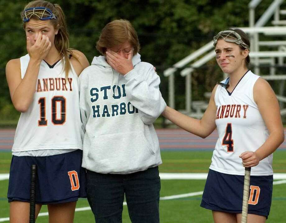 In a pre-game ceremony at the Danbury girls field hockey game at Danbury High School on Tuesday, Sept. 20, 2011, Hannah Keiser, left, Alice Dyer, center, and Liz Costanzo react to the words of Alice's daughter, Whitney Dyer, as she speaks of her father, former mayor James Dyer who recently died. Photo: Jason Rearick / The News-Times