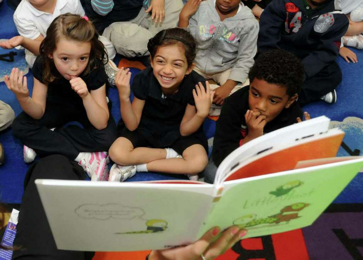 Danielle Madalon, a kindergarten teacher at K.T. Murphy Elementary school, reads the book, Little Hoot, to her class on Tuesday Sept. 20, 2011. Each student will get a copy of the book to take home courtesy of the Kiwanis Club of Stamford. From left, Kaitlyn Gray, Danielle Patrick - D Silva, Aiyden Perkins enjoy the story.