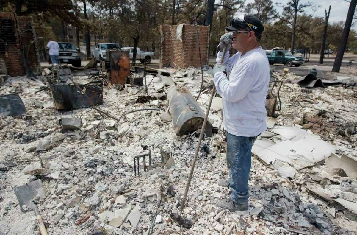 RICHARDO B BRAZZIELL : AUSTIN AMERICAN-STATESMAN FILE WHERE TO START?: Victor Coy takes a brief break last week from searching through the rubble and ashes of his home in the wake of the massive Bastrop wildfire that killed two people and destroyed more than 1,500 homes.
