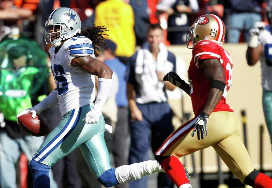 Cowboys wide receiver Jesse Holley (16) runs on a 77-yard pass reception past San Francisco 49ers safety Donte Whitner (31) in overtime Sunday. The Cowboys won 27-24. Photo: Tony Avelar/Associated Press