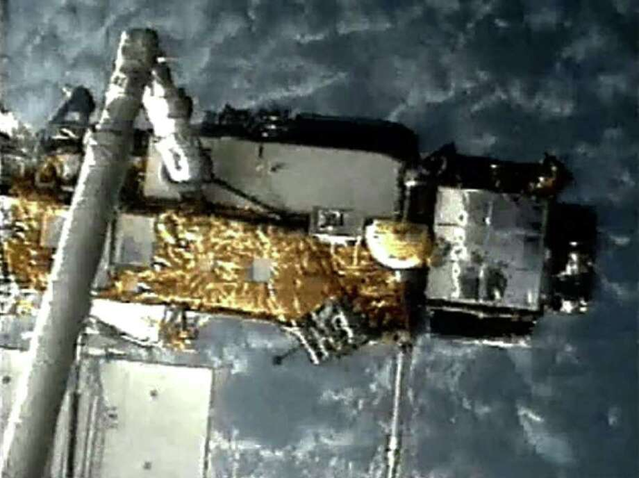 This screen grab image provided by NASA shows UARS attached to the robotic arm of the space shuttle Discovery during mission STS-48 in 1991, when UARS was deployed. NASA scientists are doing their best to predict where a plummeting 6-ton satellite will fall later this week. Photo: HOPD / NASA