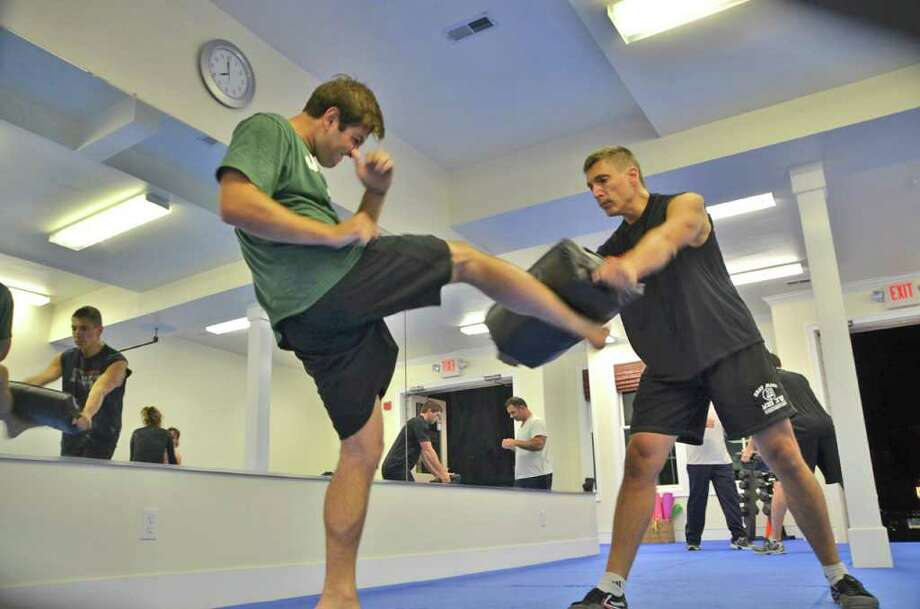 Gus Bottazzi (right), owner of Darien Krav Maga & Conditioning in Noroton, teaches self defense moves to student Bobby Brennan. Photo: Jeanna Petersen Shepard