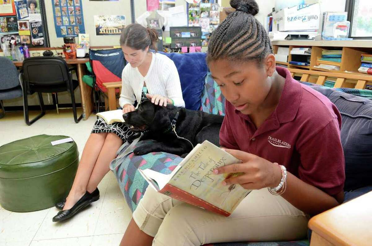 Amber Edghil-Cofield, 12, reads The Tale of Despereaux by Kate DiCamillo with reading teacher Jamie Waggaman and Eli, a therapy dog, at DOMUS in Stamford, CT on Wednesday September 21, 2011.