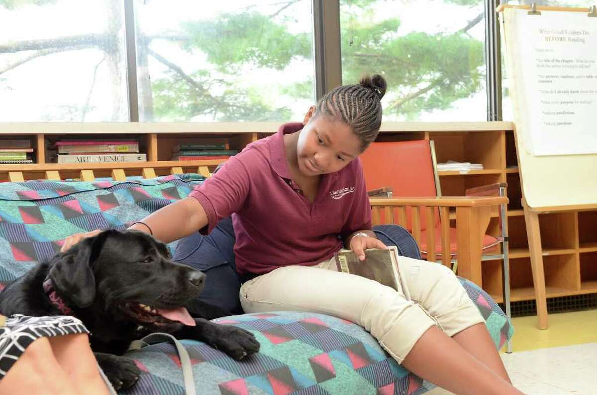 Amber Edghil-Cofield, 12, reads The Tale of Despereaux by Kate DiCamillo with Eli, a therapy dog, at DOMUS in Stamford, CT on Wednesday September 21, 2011.