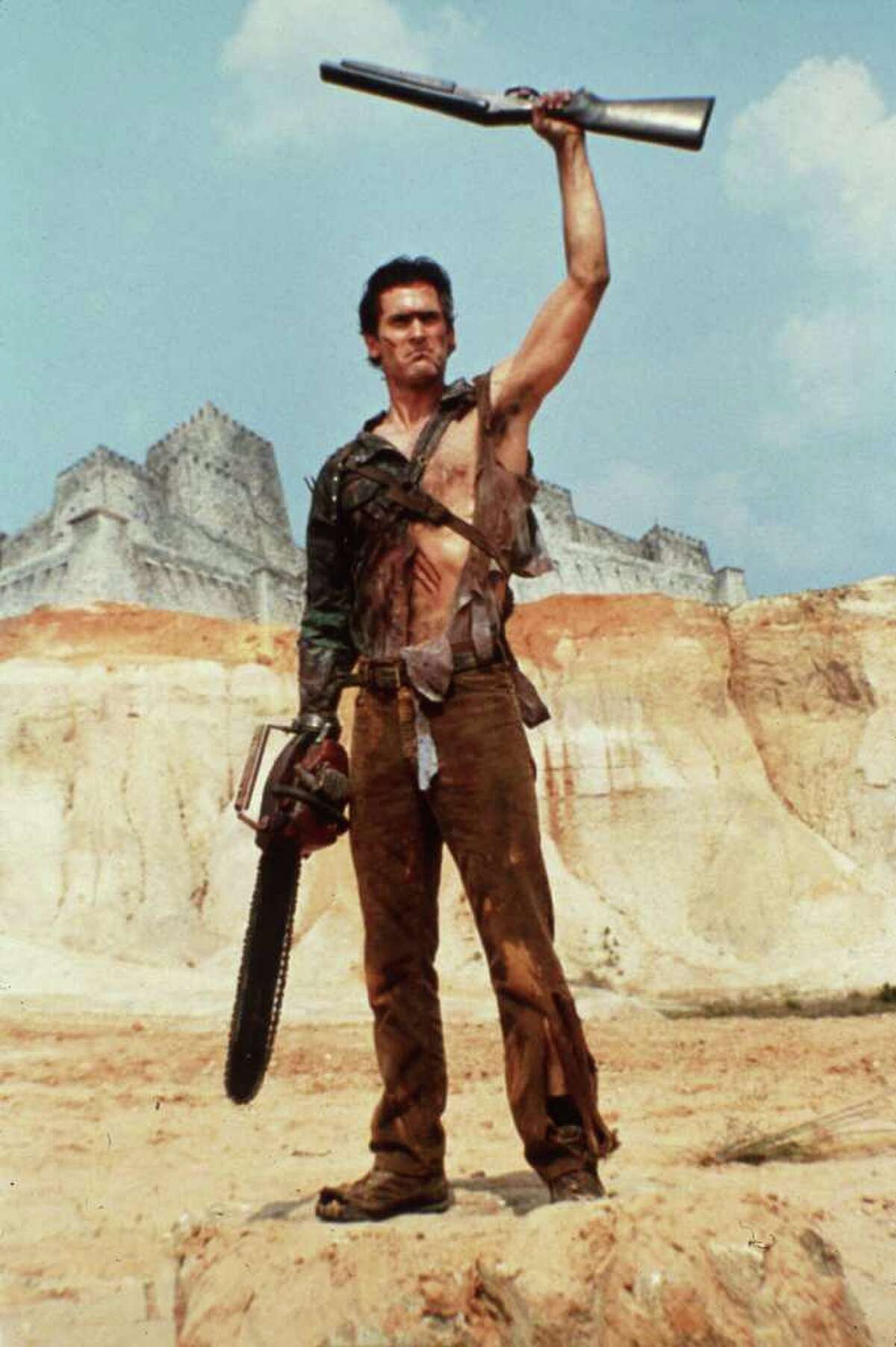 """EVIL DEAD 2 -- Bruce Campbell starred in the 1987 film Evil Dead II. HOUCHRON CAPTION (07/02/2005) SECSTAR COLOR: VIOLENT SIDE: Actor Bruce Campbell is well-armed in a scene from the 1987 film """"Evil Dead II."""""""