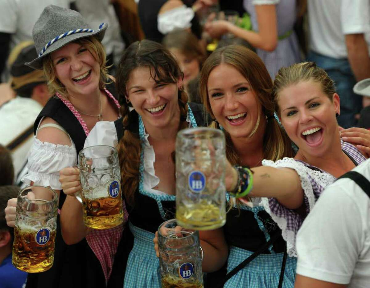 Visitors of the Oktoberfest beer festival pose with beer mugs in a beer tent at the Theresienwiese fair grounds in Munich, southern Germany, on September 17, 2011. The world famous beer festival, which is excepted to attract around six million visitors, is running until October 3, 2011. AFP PHOTO/CHRISTOF STACHE