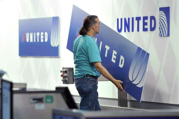 Brian Kersey : Associated Press File OUT WITH THE OLD: Steve Reininger removes a sign with the old United Airlines logo to reveal the new logo featuring the Continental Airlines blue globe at a ticket counter at O'Hare International Airport, Tuesday, May 17, 2011. In addition to changing the signage at O'Hare Airport, the merging airlines will combine check-in kiosks at 83 airports Wednesday allowing travelers to check in for flights on either airline. (AP Photo/Brian Kersey)
