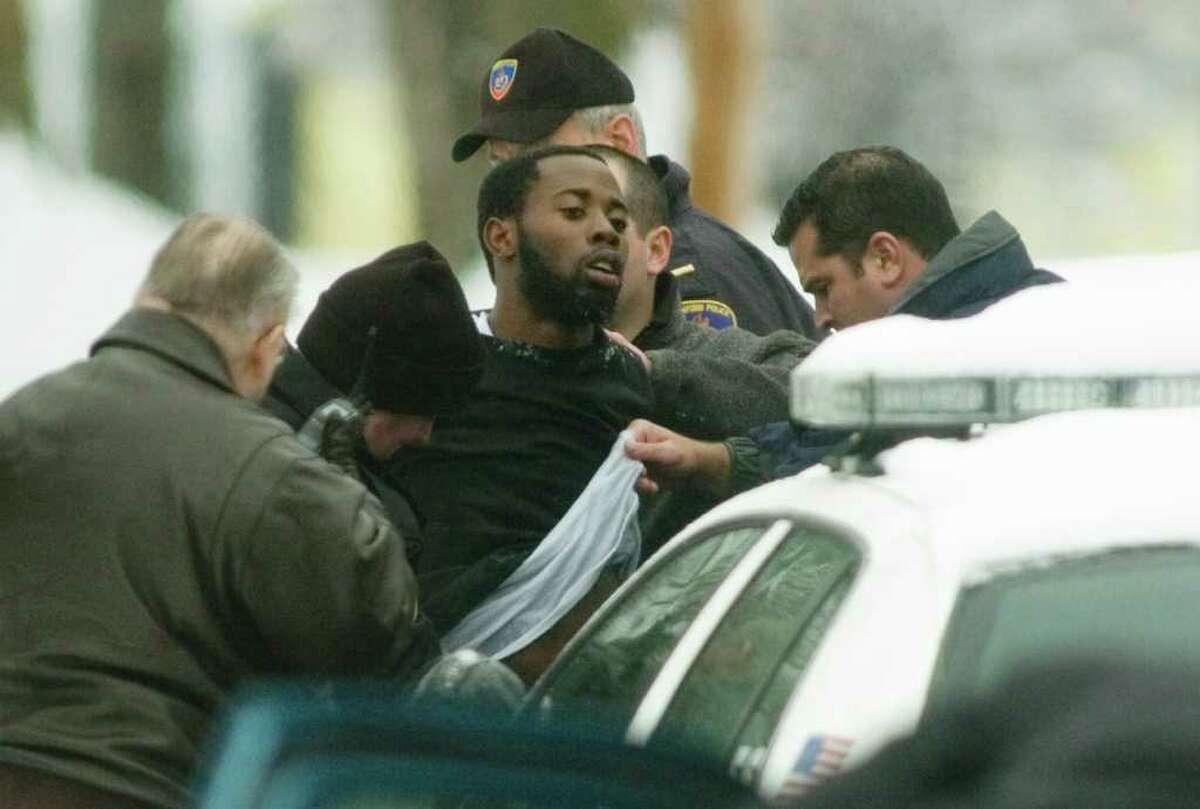 Stamford police officers search a suspect, Edens Gabriel, of 42 Valley View Road, Norwalk, who was taken into custody near 40 Woodmere Road after a bank robbery that was reported at 2:37 p.m. in Stamford, Conn. on Friday, Feb. 22, 2008. Chris Preovolos/Staff photo