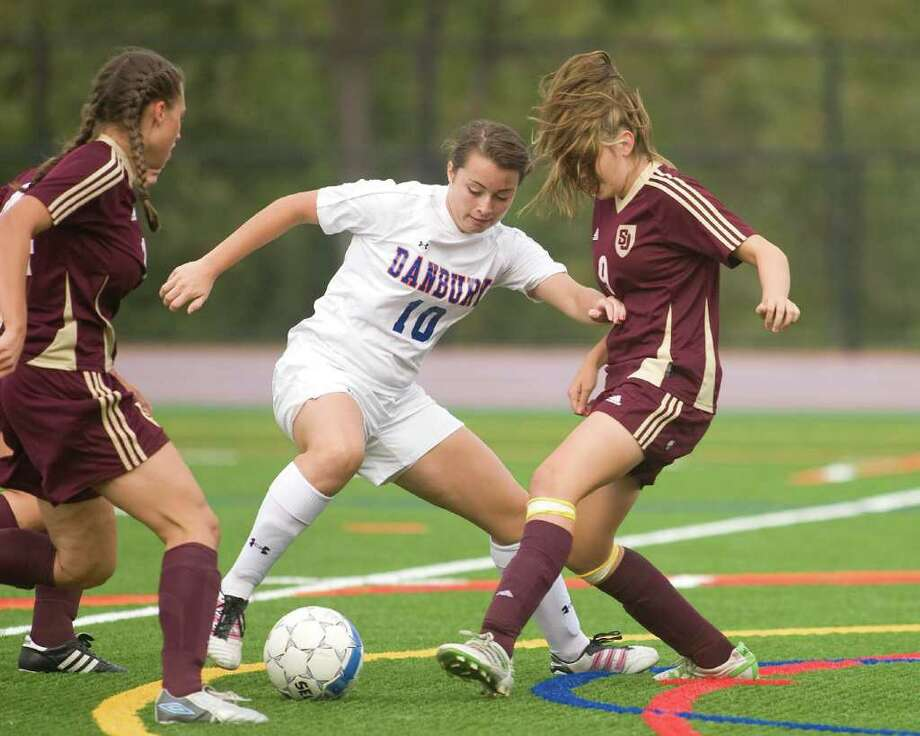 Danbury's Daniela Varela (10) battles for the ball with St. Joseph's Sabrina Toole, right, and Jessica Jowdy Wednesday at Danbury High School. Photo: Barry Horn / The News-Times Freelance