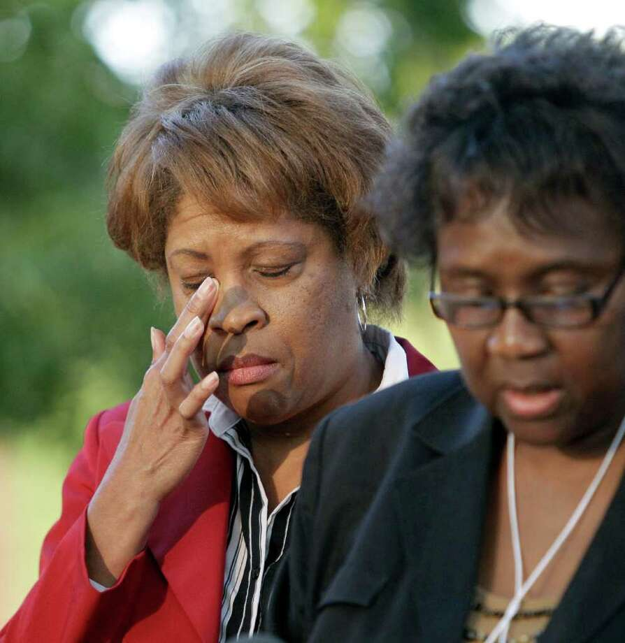 Louvon Harris, left, wipes her eye as she listens to Clara Taylor, right, both sisters of James Byrd Jr., as she reads a statement after witnessing the execution of Lawrence Russell Brewer Wednesday, Sept. 21, 2011, in Huntsville, Texas. Brewer, 44, one of two purported white supremacists condemned for the dragging death of James Byrd Jr., was executed Wednesday. Brewer was convicted for his participation in chaining Byrd to the back of a pickup truck, dragging the black man along a rural East Texas road and dumping what was left of his shredded body outside a black church cemetery in 1998. (AP Photo/David J. Phillip) Photo: David J. Phillip, Associated Press / AP