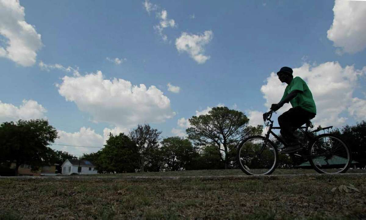 """Charles Pruitt, 58, rides his bike through Emancipation Park Wednesday, Sept. 21, 2011, in Houston. Emancipation Park on the corner of Elgin and Dowling received a $1 million grant from the Texas Parks and Wildlife Commission that brings the city about three-quarters of the way to raising the $10.5 million needed for a planned redevelopment of the historic park in the Third Ward city officials said Wednesday. Plans include an """"iconic"""" piece of sculpture and a new amphitheater for concerts. The park was founded by ex-slaves in 1872. """"This park means a lot,"""" Pruitt said who comes to the park almost daily. """"It has a lot of history behind it."""" ( Johnny Hanson / Houston Chronicle )"""