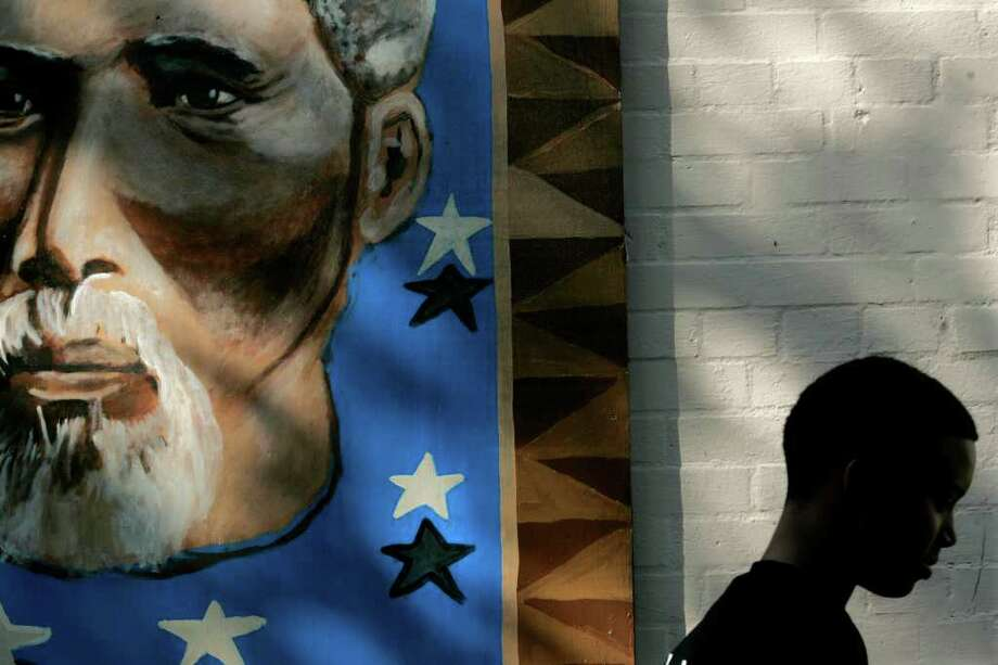 Domonique Davis, 12, walks past a mural with the image of Rev. Jack Yates while returning to the Emancipation Park community center from the playground.  The 10-acre park, originally purchased by a group of freed slaves, including Yates, was founded to commemorate their emancipation from slavery. Photo: Johnny Hanson, For The Chronicle / Freelance