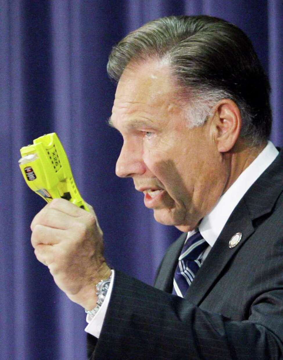 Orange County, Calif., District Attorney Tony Rackauckas shows a Taser of the type used as he announces that two police officers will be charged in the death of Kelly Thomas, a mentally ill homeless man, at a news conference in Santa Ana, Calif., Wednesday, Sept. 21, 2011. Fullerton, Calif., police officer Manuel Ramos was charged with one count each of second degree murder and involuntary manslaughter in the death of Thomas after a violent confrontation with police officers on July 5. Police Cpl. Jay Cicinelli was charged with one count each of involuntary manslaughter and excessive force. (AP Photo/Reed Saxon)