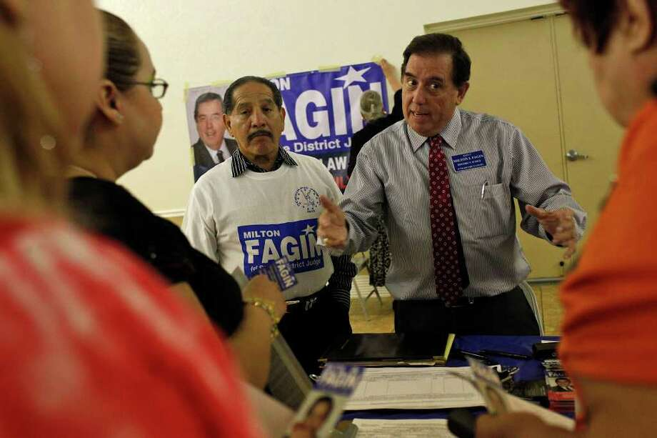 Milton Fagin (right), a Democratic candidate for the 37th District Court — with supporter Al Esparza (left) — talks to voters. The Bexar County Democratic Party says it's focused on winning back seats — and paying off debt. Photo: Lisa Krantz/lkrantz@express-news.net / SAN ANTONIO EXPRESS-NEWS