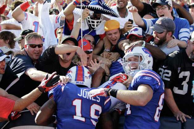 Buffalo Bills' David Nelson, center,  celebrates his game-winning touchdown reception with fans and Bills' Donald Jones, left, and Scott Chandler (84) during the fourth quarter of an NFL football game against the Oakland Raiders in Orchard Park, N.Y., Sunday, Sept. 18, 2011. The Bills won 38-35. Photo: David Duprey, AP / AP