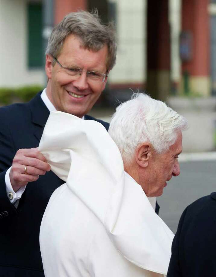 German President Christian Wulff, left, adjusts the robe of Pope Benedict XVI, right, after he arrived at Tegel airport in Berlin, Germany, Thursday, Sept. 22, 2011. Pope Benedict XVI is on a four-day official visit to his homeland Germany. Photo: Gero Breloer, AP / AP