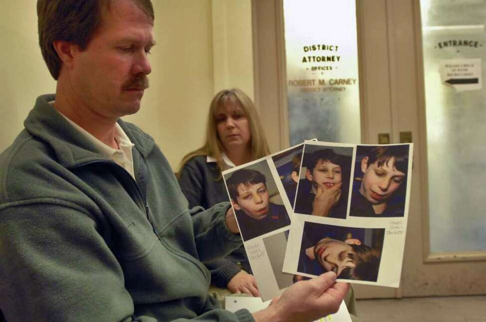 Michael and Lisa Carey wait outside of the Schenectady County District Attorney's office in November 2007. Their son, Jonathan, died while under the care of state workers earlier that year. Michael holds pictures of a bruised and injured Jonathan from December 2005. (Times Union Staff Photograph by Philip Kamrass)