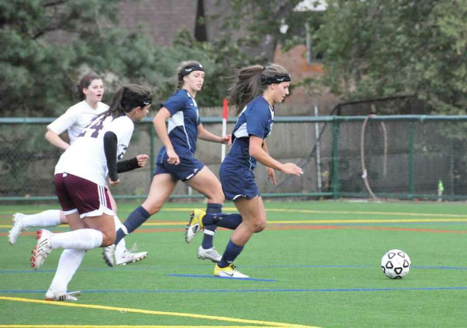 Greens Farms Academy junior Phebe Wong of Darien (right) scored seven goals in GFA's two victories last week to help the Dragons remain undefeated. Photo: Contributed Photo