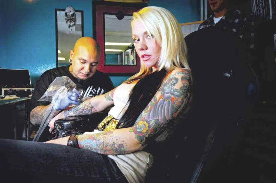 Beaumont tattoo artist Mundo Trevino, left, works on a tattoo for his wife and co-owner, Aubrey Trevino, during a recent visit to their shop, Tattoos by Mundo, on Calder Avenue.  Wednesday,  September 7, 2011.  Valentino Mauricio/The Enterprise Photo: Valentino Mauricio