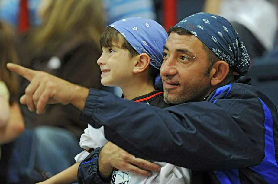 Kyle Abate, 6, of Colonie and his father Saverio Abate enjoy watching an NHL exhibition game between the New Jersey Devils and the New York Rangers at the Times Union Center in Albany, N.Y. Wednesday, Sept. 21, 2011. (Lori Van Buren / Times Union) Photo: Lori Van Buren