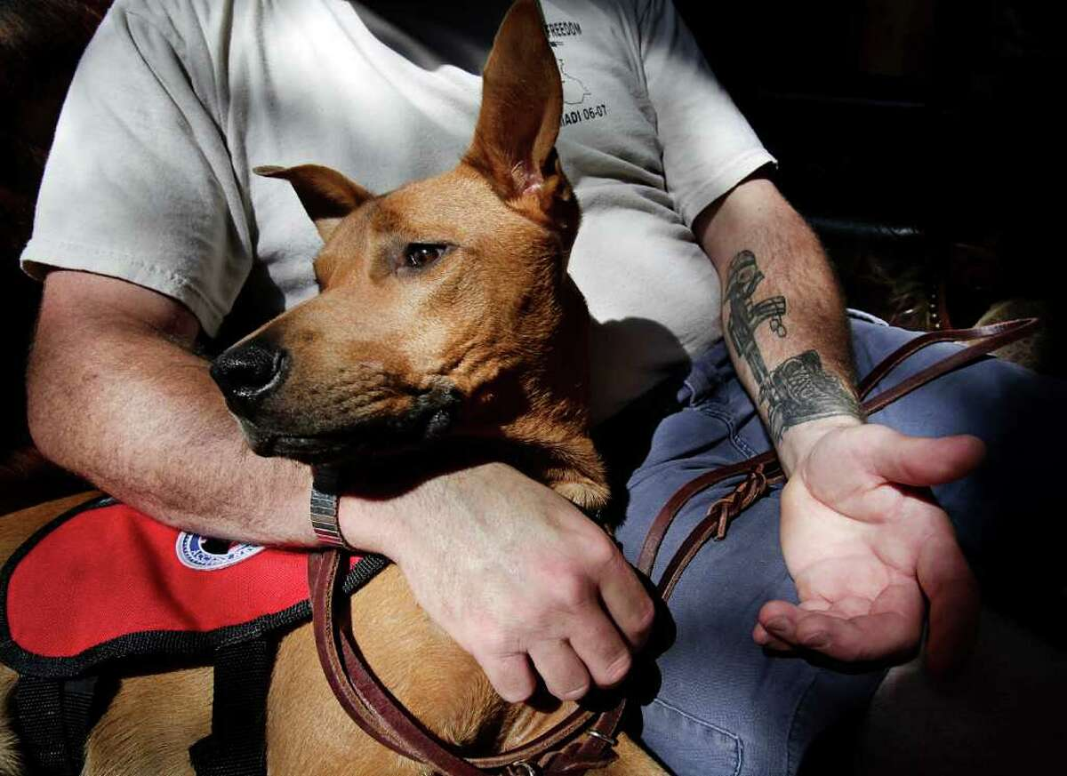 Army Sgt. Jeremiah Honaker relaxes after a training walk with his service dog, Gunny. Honaker, who is dealing with PTSD, says he can, at times, be uncomfortable in public. Gunny has been trained to detect stressful situations.