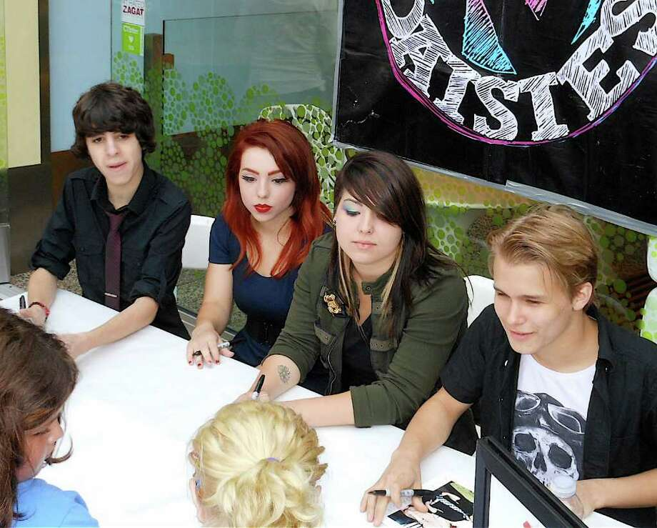 The rising rock band, Kicking Daisies -- local musicians, from left, Ben Spremulli, Carly Kalafus, Caitlin Kalafus and Duran Visek -- greeted fans and autographed CDs Tuesday in front of Pinkberry on the Post Road. Photo: Mike Lauterborn / Fairfield Citizen contributed