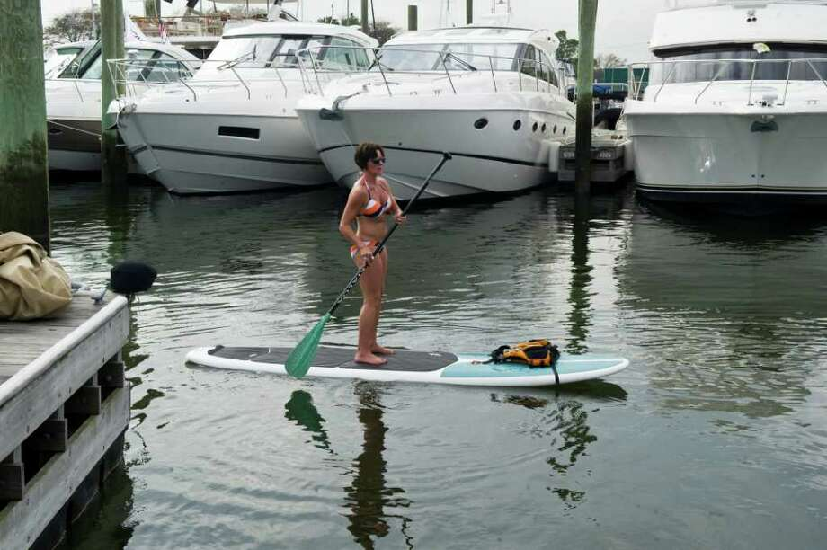 """Yoga instructor Patricia Cuomo demonstrates her """"Paddlepalooza"""" moves doing yoga on a surf board during the 2011 Norwalk Boat Show at Norwalk Cove Marina, Calf Pasture Beach in Norwalk, Conn., Sept. 22, 2011. The show is open to the public and runs through Sunday featuring live music, informational seminars about boating and fishing and special events catering to kids. Photo: Keelin Daly / Stamford Advocate"""