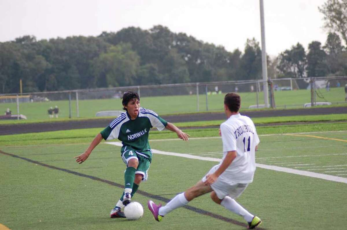Alejandro Rivera, of the Norwalk High boys soccer team, tries to weave around Trumbull's Manny Pereira during the Eagles' 2-0 win on Thursday.