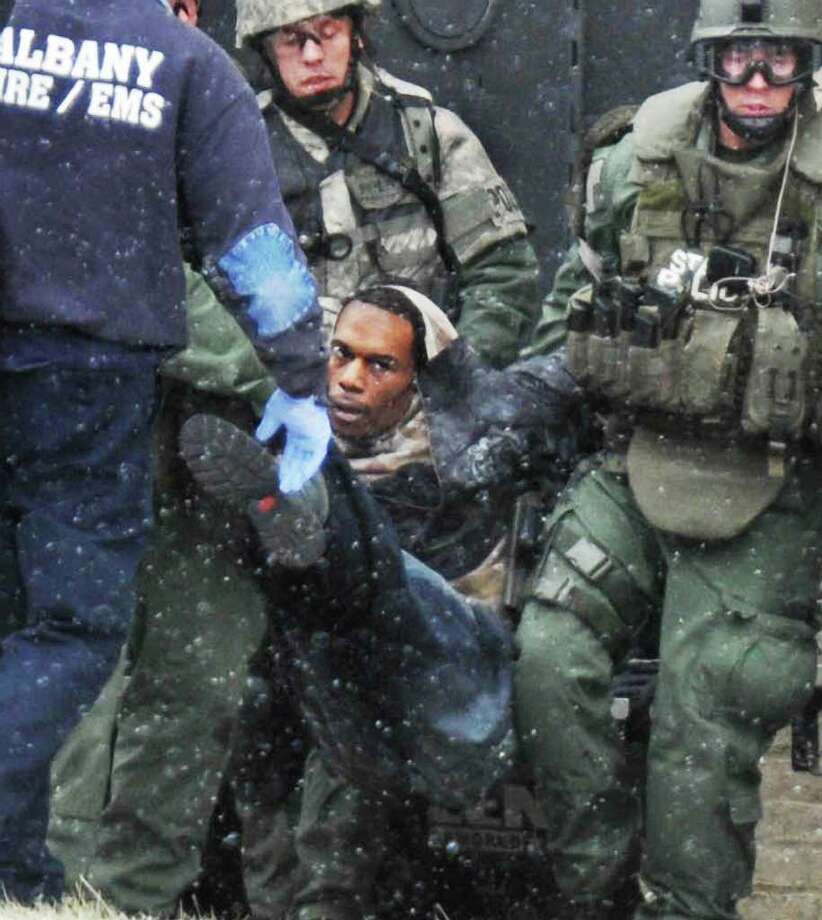 Police take Isaac Peterson into custody following a hostage situation on Westerlo Street in Albany from an armored car Friday morning December 23, 2010.  (John Carl D'Annibale / Times Union) Photo: John Carl D'Annibale