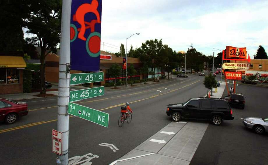 A bicycle rider has to swerve as a car pulls out into traffic on NE 45th Street in Seattle's Wallingford neighborhood. The stretch of road in front of Dicks Drive-In is the most dangerous in the city for bicyclists, with over 6 collisions there over three years. Photo: JOSHUA TRUJILLO / SEATTLEPI.COM