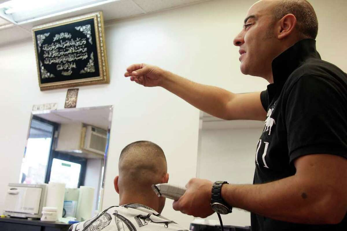 The shop of barber Amine Darhbach, a U.S. citizen from Morocco and located off Steinway Street in Astoria, N.Y., had been under scrutiny by the New York Police Department as part of a secret program to gather intelligence on the city's Moracann population, is interviewed as he cuts hair, Friday, Sept. 2, 2011. The New York Police Department subjected American citizens to surveillance and scrutiny, not because of any wrongdoing but because of their ethnicity. Documents obtained by The Associated Press describe a secret program known as the Moroccan Initiative, which catalogued where people of Moroccan ancestry shopped, ate and prayed. (AP Photo/Charles Dharapak)