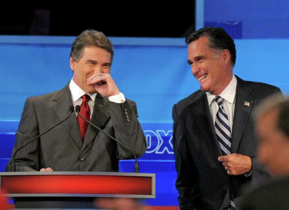PHELAN M. EBENHACK : ASSOCIATED PRESS LIGHT MOMENT: Rick Perry, left, and Mitt Romney had some heated exchanges during the Fox News/Google debate Thursday night, but it wasn't all scowls and seriousness. Photo: Phelan M. Ebenhack / FR121174 AP
