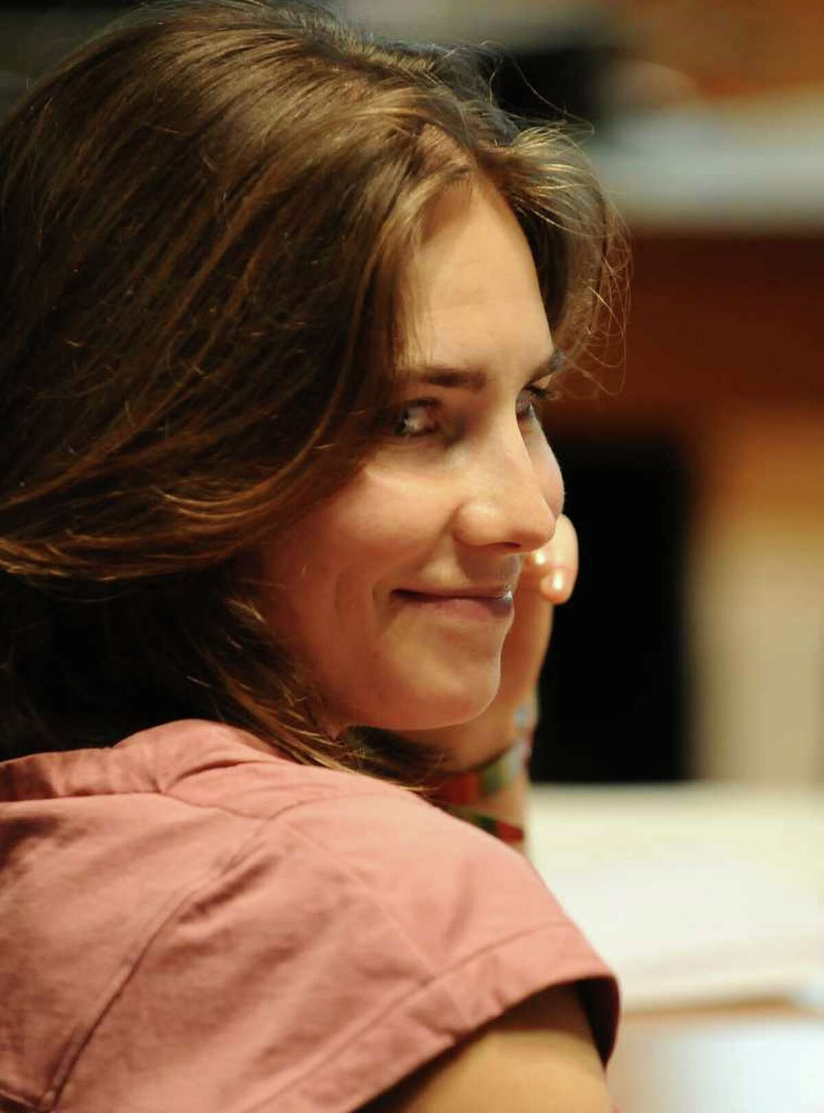 Amanda Knox smiles in court on Friday as her appeal trial against her conviction for the murder of British housemate Meredith Kercher is winding up, with prosecutors set to present their final arguments. AFP PHOTO/MARIO LAPORTA