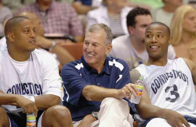 Connecticut head basketball coach Jim Calhoun, center, shares a smile with former players Tate George, left, and Caron Butler During the Jim Calhoun Celebrity Classic basketball game at the Mohegan Sun Arena in Uncasville, Conn., on Saturday Aug. 8, 2008. George has been indicted on federal fraud charges for his role in a $2 million investment scheme.  (AP Photo/Fred Beckham) Photo: Fred Beckham, ASSOCIATED PRESS / AP2008