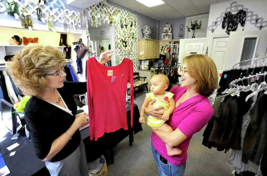 Diane Kozenieski, left, helps shopper Kim Skerencak, who holds her baby, Peightyn, 10 months old, in Kozenieski's Newtown business, Such-A-Deal, Thursday, Sept 22, 2011. Photo: Michael Duffy / The News-Times
