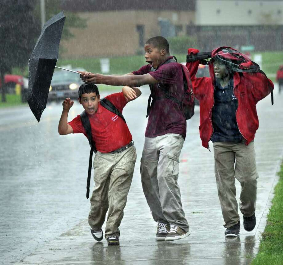 From left, Anthony Sanchez, 11, Dominique Rogers, 14 and Tykeem Gibbs, 13, walk home from school in heavy rain Friday. The kids are students at Pathways Academy in Danbury. Photo taken Friday, Sept. 23, 2011. Photo: Carol Kaliff