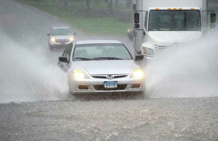 A car sprays up water while going through a puddle on West Putnam Avenue while exiting Greenwich heading into New York state during an afternoon rain storm, Friday afternoon, Sept. 23, 2011. Photo: Bob Luckey / Greenwich Time
