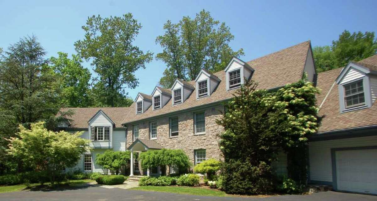 This custom-built colonial at 4 Fox Run Lane, the road's only structure, offers a quiet setting for its inhabitants. The 2-acre property includes a Gunite pool with Asian influences.